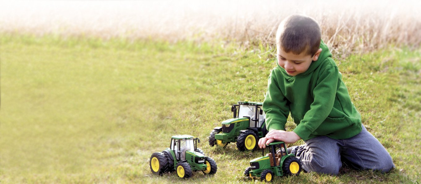 Boy playing in the grass with tractors