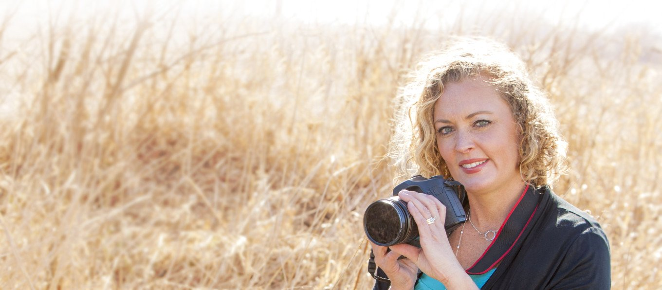 Woman holding a camera next to a field of tall grass