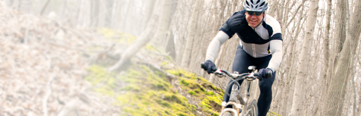 mountain biker on a wooded trail with a shoulder wrap on