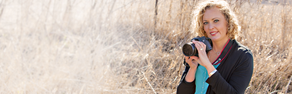 woman with blonde curly hair holding a camera in a grassy field