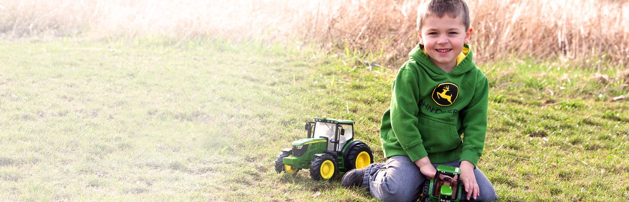 little boy in a John Deere green hoodie playing with tractors in the grass